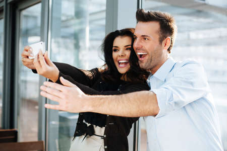men talking: Happy colleagues taking a selfie with a smartphone