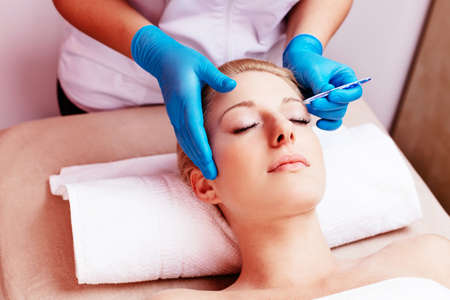 regulating: Young woman having her eyebrows regulated at a beautician Stock Photo