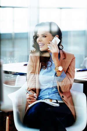 Junge lächelnde Frau im Gespräch auf dem Handy und sich Notizen Lizenzfreie Bilder