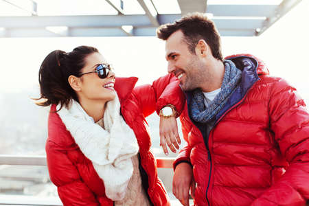 sun down: Happy couple enjoying time together at winter time wearing down jacket