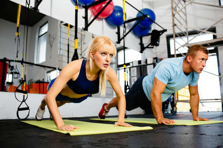 atractive: Photo of a woman doing pushups in a gym withe her personal trainer Stock Photo