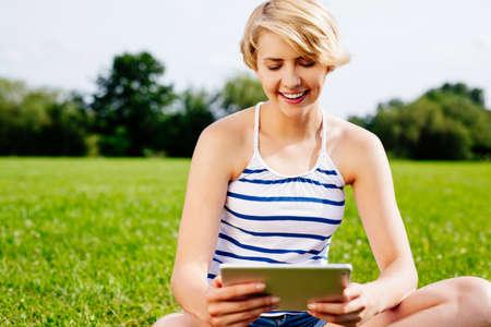 Junge hübsche Frau sitzt auf dem Rasen und die Bahn auf einer digitalen Tablette surfen Lizenzfreie Bilder