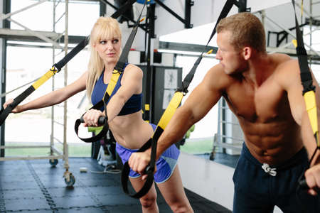 straps: Photo of a muscular couple working out on suspension straps Stock Photo