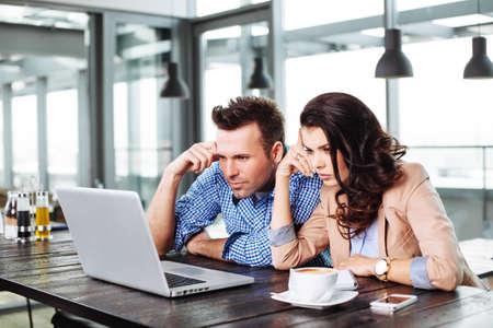 Junge nachdenklich Paar vor einem Laptop-Display photo