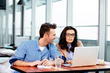 Junge Paare, die zusammen an einem Laptop arbeiten photo