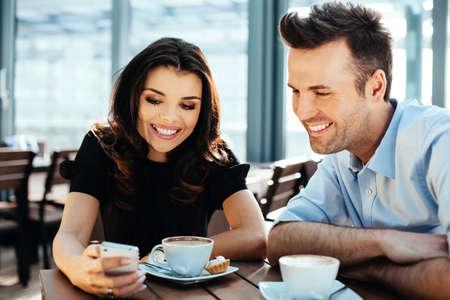 Zwei junge Profis Fotos auf einem Smartphone und Kaffee zu trinken Surfen photo