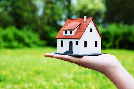 Photo of a house miniature against a green leafy background photo
