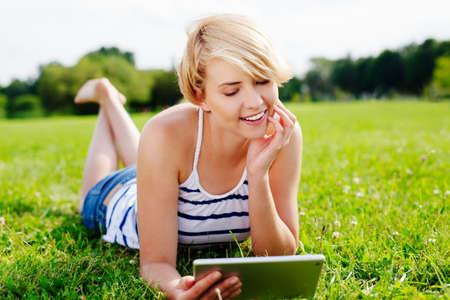 Foto von eine hübsche Frau lag im Park und das Surfen im Web auf ihrem Tablet photo