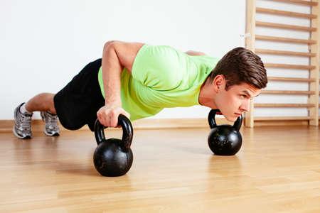 Junger Mann tun Push-ups auf Kettle Gewichte photo