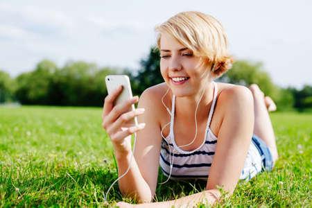 Foto von einer attraktiven Frau glücklich entspannt auf dem Rasen und die etwas Musik hört photo