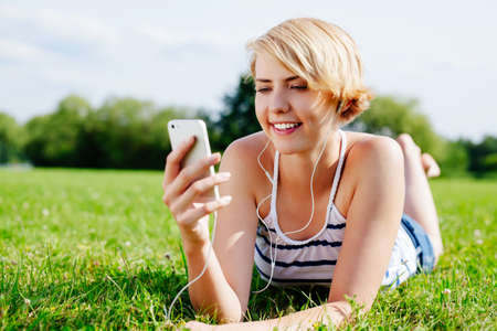 Photo of an attractive happy woman relaxing on the grass and listening to some music photo