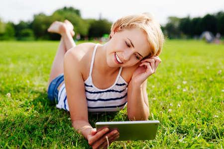Foto einer jungen blonden Frau entspannt auf dem Rasen und schaut in ihrem Tablet photo