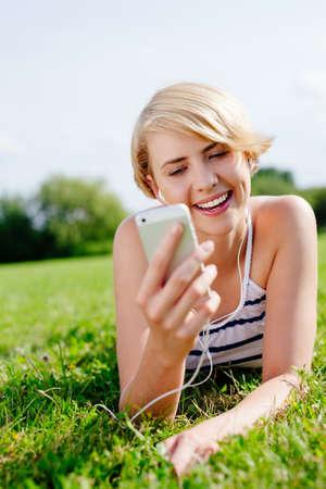 Portrait einer attraktiven blonden Frau mit Kopfhörern auf dem Rasen lag photo
