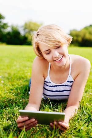 Portrait einer Frau mit einem digitalen Tablet, während im grünen photo