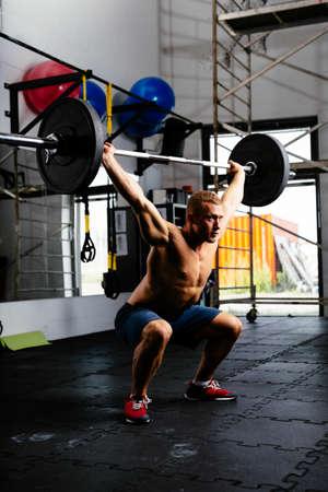 Muskulöser Mann mit Hantel in einem Training