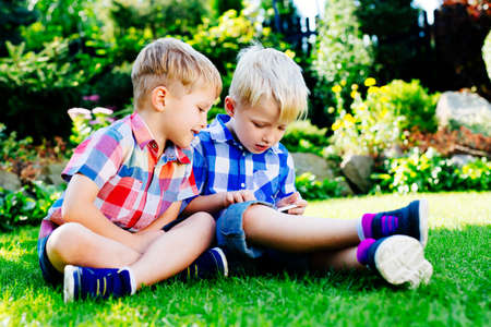 Young boys playing on smartphone at garden Imagens
