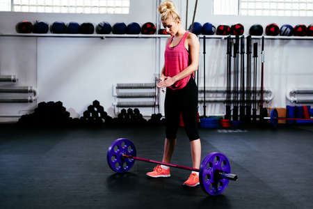 Young woman concentrate before barbells exercise at gym Stock Photo