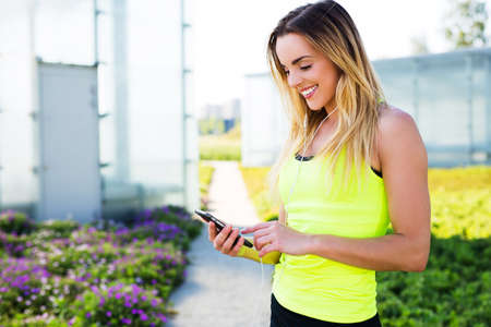 Young happy runner checking her smartphone