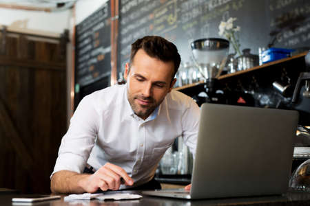 Happy cafe manager counting recipes with laptop