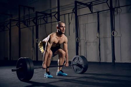Shirtless man lifting barbells at gym