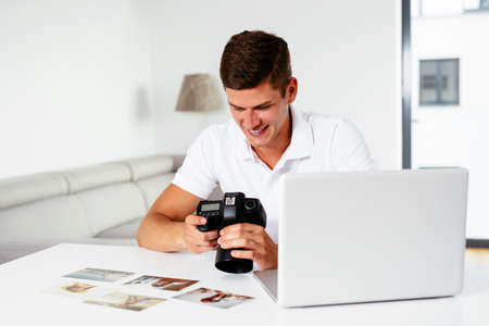 Young photographer browsing his pictures on DSLR Camera