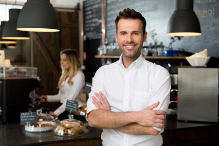 Successful small business owner standing with crossed arms with employee in background preparing coffee Stock Photo
