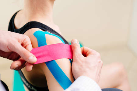 Kinesiotaping. Physical therapist applying tape to patient shoulder Фото со стока - 96466258