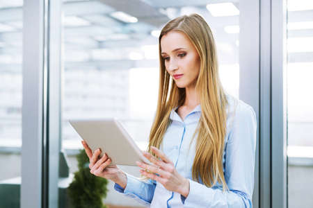 Businesswoman standing in an office and holding a digital tablet