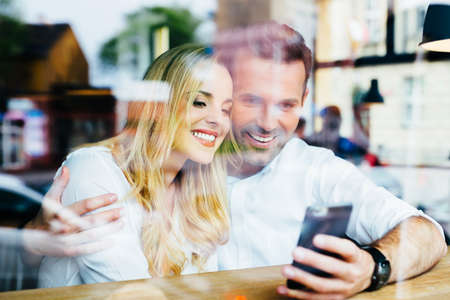 Young couple have fun while looking on smartphone at cafe