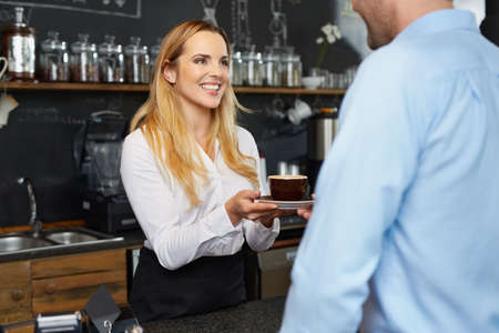 Jolie barista offrant tasse de café au restaurant de travail Banque d'images - 96522829