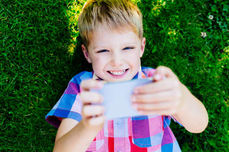 Young boy playing with smartphone, laying on grass