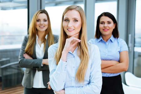 Three confident business associates gathered in an office room and looking at the camera Stock Photo