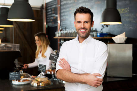 Happy small business owner standing at front of bar with employee in background preparing coffee Stock Photo - 96002539