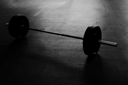 Black and white picture of barbells on the gym floor