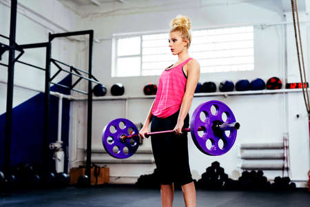Young woman training with barbells at gym