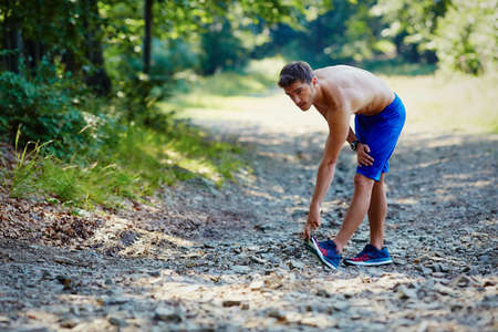 Runner suffers from calf cramp during run exercise in mountains Stock fotó - 96578859