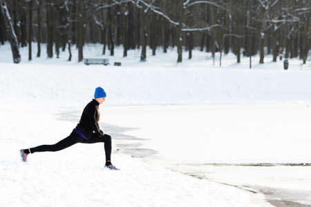 Young woman stretches during winter run Stock fotó
