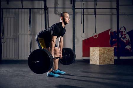 Young man lifting barbells at gym