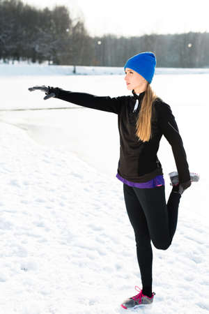 Young woman stretching after winter run
