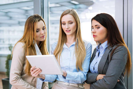 Group of three young female entrepreneurs looking at a digital tablet and talking Archivio Fotografico