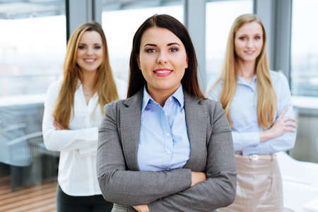 Three female business partners posing in an office