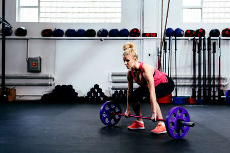 Young motivated woman training deadlift with barbells at gym