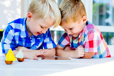 Happy twins playing together on digital tablet