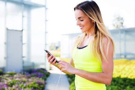 Young woman looking at smartphone before running exercise