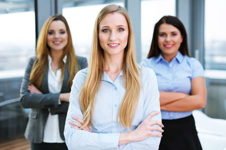 Three female business partners standing in an office and looking at the camera Stock Photo