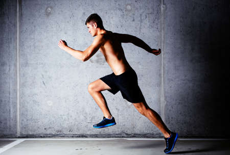 Runner sprinting against concrete wall in garage Stock Photo