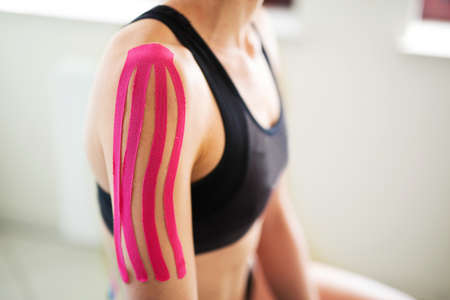 Injured woman having kinesiology on her shoulder, arm Stock Photo