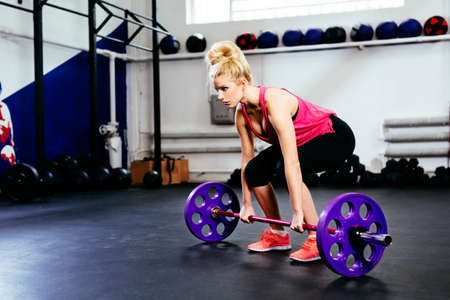 Young woman training deadlift with barbells at gym