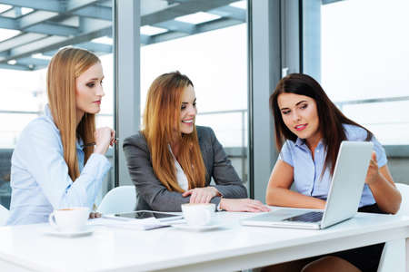 Three businesswomen sitting in an office and discussing an online project Stock Photo
