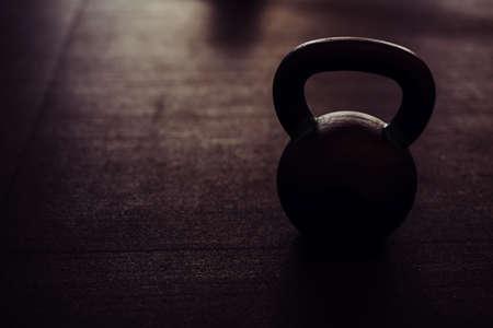 silhouette of heavy kettlebell on black floor Фото со стока
